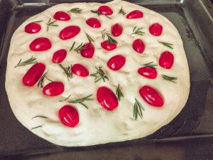 Focaccia mit Tomaten, Romarin und Öl belegen